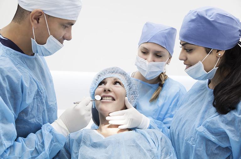 Una mujer rodeada de doctores que le están realizando una cirujía dental en Diparr